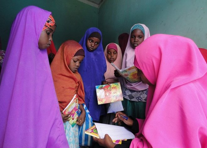 Photo of IDP mums studying alongside children at free camp school in Adado, central Somalia